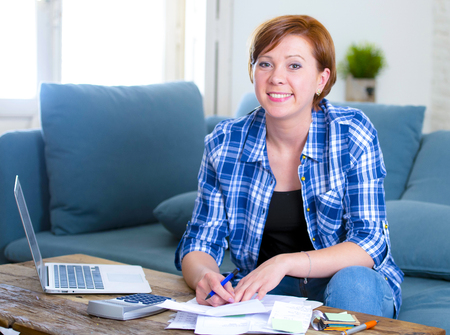 young attractive and happy 30s red hair woman banking and working domestic finance accounting at home couch with computer and calculator smiling confident and satisfied in financial success