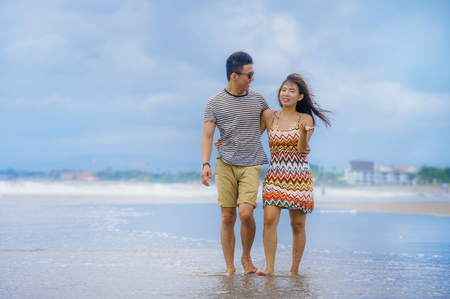young beautiful and Asian Chinese romantic couple walking together embracing on the beach happy in love enjoying holidays and relax smiling joyful in tourism trip and romance concept Stock Photo