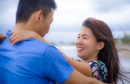 young happy and beautiful Chinese Asian couple with woman hug her boyfriend romantic and cuddle on the beach smiling in dating and romance concept celebrating Valentines