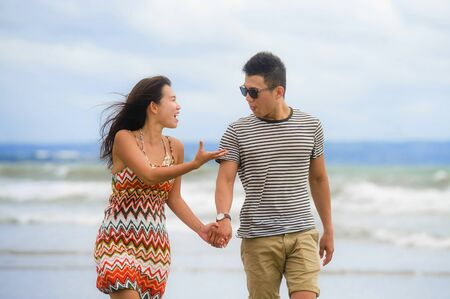 young beautiful and Asian Chinese romantic couple walking together on the beach happy in love enjoying holidays arguing with girlfriend nagging and boyfriend taking tongue out