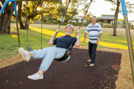 playful and happy senior American couple around 70 years old enjoying at swing park with husband pushing wife smiling and having fun together in mature lifestyle and love concept Imagens