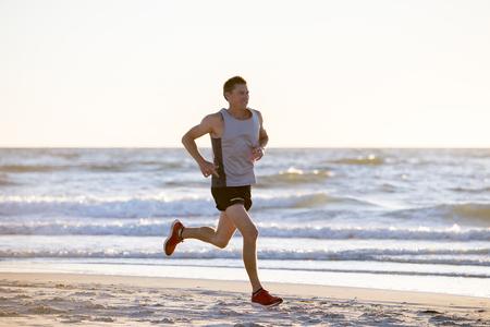 portrait, de, jeune, fit sportif, et, coureur fort, homme, formation, sur, été, coucher de soleil, plage, dans, mer, courant, de, fitness Banque d'images