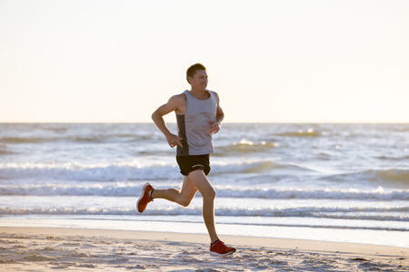 portrait of young athletic fit and strong runner man training on Summer sunset beach in sea shore running and fitness workout in sport and healthy lifestyle concept