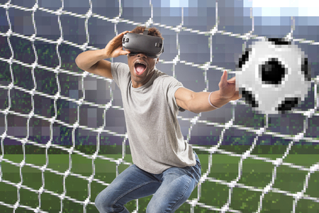 young attractive black afro American man using vr virtual reality 3D goggles playing soccer football video game with pixelated computer goal and stadium background in gaming fun concept Stock Photo