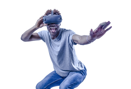 young active excited afro American man enjoying happy playing with 3d goggles virtual reality video device in gaming and entertainment new technology concept isolated background Standard-Bild