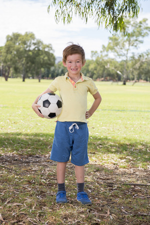 young little kid 7 or 8 years old enjoying happy playing football soccer at grass city park field posing smiling proud standing holding the ball in childhood sport passion and healthy lifestyle concept