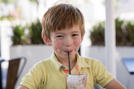 head portrait of lovely and sweet young kid 7 or 8 years old in yellow shirt  enjoying happy drinking ice cream smoothie milk shake with straw in childhood and lifestyle concept