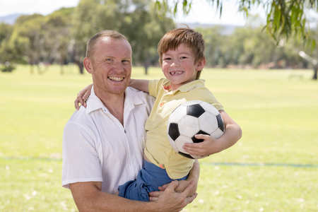 young happy father carrying on his back excited 7 or 8 years old son playing together soccer football on city park garden posing sweet and loving holding the ball in dad and boy relationship Stock Photo