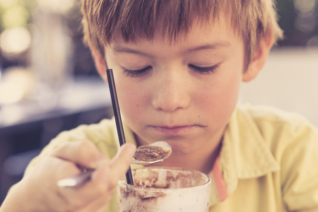 head portrait of lovely and sweet young kid 7 or 8 years old in yellow shirt  enjoying happy drinking ice cream smoothie milk shake with spoon in childhood and lifestyle concept