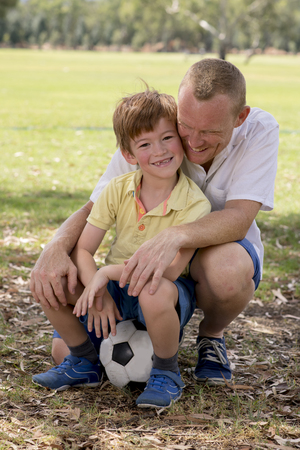 young happy father and excited 7 or 8 years old son playing together soccer football on city park garden posing sweet and loving holding the ball in dad and boy relationship and healthy lifestyle
