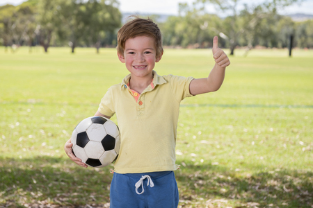 young little kid 7 or 8 years old enjoying happy playing football soccer at grass city park field posing smiling proud standing holding the ball in childhood sport passion giving thumb up ok hand sign