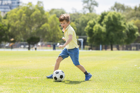 young little kid 7 or 8 years old enjoying happy playing football soccer at grass city park field running and kicking the ball excited in childhood sport passion and healthy lifestyle concept Stock Photo