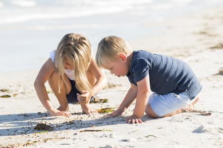 小さな兄弟抱擁と家族や子供のライフスタイルのコンセプトで休日や夏を楽しむ美しいブロンドの若い姉妹と砂のビーチで一緒に遊ぶ小さな愛らし