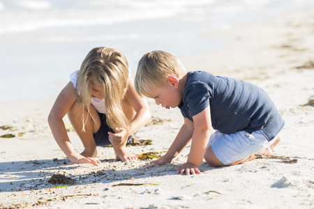 little adorable and sweet siblings playing together in sand beach with small brother hugging and beautiful blond young sister enjoying holidays and Summer in family and children lifestyle concept Stock Photo