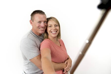 young beautiful happy and attractive romantic couple with husband and wife or girlfriend and boyfriend taking selfie self portrait photo with stick and mobile phone camera isolated on white background