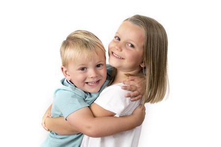 7 jaar oud schattig blond gelukkig meisje poseren met haar kleine 3 jaar oude broer glimlachen vrolijk geïsoleerd op witte achtergrond in kinderen en broers en zussen relatie concept