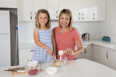 attractive blond 30s woman cooking and baking happy together with sweet adorable mini chef little girl at home modern kitchen in mother and daughter love education and family lifestyle concept   Banque d'images