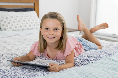 sweet and beautiful blond 6 or 7 years old young girl lying on bed smiling happy using the internet on digital tablet pad watching and having fun in child relationship with technology concept Banque d'images