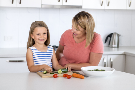 young attractive woman cooking together with her sweet beautiful blond little 6 or 7 years old daughter smiling happy preparing salad in vegetable nutrition education and healthy lifestyle concept  Stock Photo