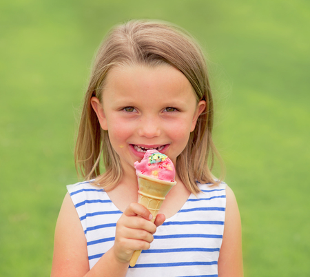 portrait of adorable and beautiful blond young girl 6 or 7 years old eating delicious ice cream smiling happy isolated on green grass field background in childhood lifestyle concept