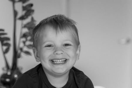 head and shoulders portrait of blond beautiful 3 or 4 years old caucasian kid smiling happy and excited isolated at home in lifestyle concept in black and white