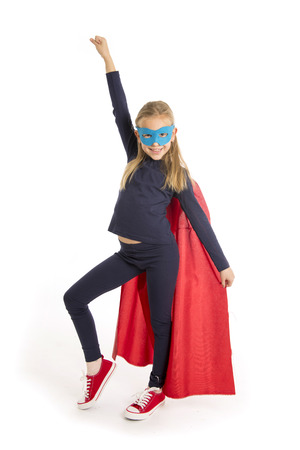 7 or 8 years old young female schoolgirl child in super hero costume performing happy and excited isolated on white background in leadership success courage and fantasy concept