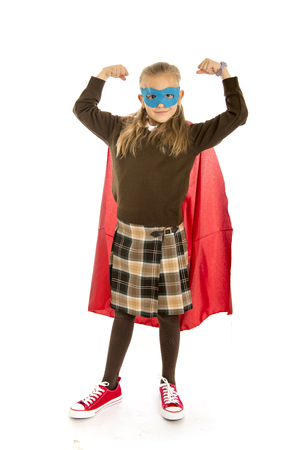 7 or 8 years old young female child in super hero costume over school uniform  performing happy and excited isolated on white background in leadership success courage and fantasy concept Stock Photo