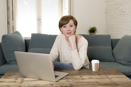young attractive and happy woman at home sofa couch doing some laptop computer work smiling relaxed in entrepreneur lifestyle and freelance job success concept