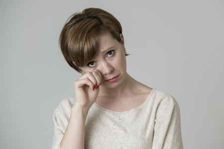 young pretty and sad red hair woman looking worried and depressed crying and suffering pain and depression in life problem concept isolated on even background studio portrait