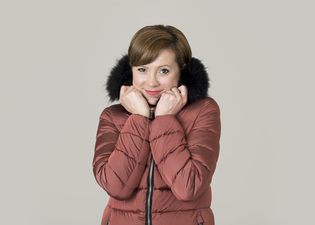 young attractive and happy red hair Caucasian woman on her 20s or 30s posing cheerful and smiling wearing warm winter jacket with fur hood isolated on grey background in seasonal fashion concept