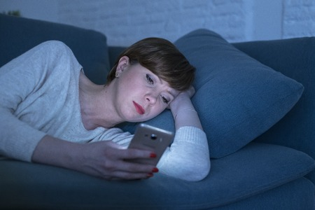 portrait of young woman 30s lying on bed couch late at night at home using social media app on mobile phone tired and sleepy in internet addiction concept