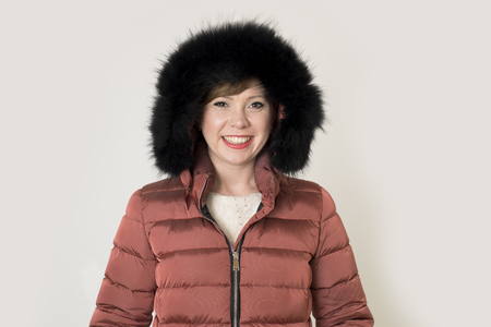 young attractive and happy red hair Caucasian woman on her 20s or 30s posing cheerful and smiling wearing warm winter jacket and fur hood isolated on grey background in seasonal fashion  版權商用圖片