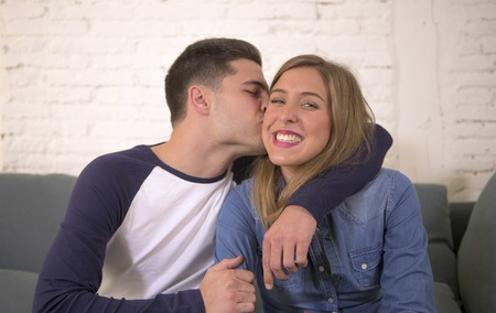 young attractive happy and romantic couple boyfriend and girlfriend cuddle tender at home couch smiling playful in beautiful teenagers love and relationship concept