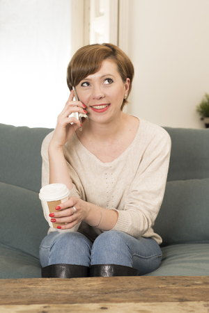 young attractive and happy red hair woman sitting at home sofa couch drinking coffee talking on mobile phone relaxed in communication and lifestyle concept