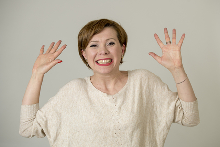 portrait of young happy and pretty red hair woman on her 30s in sweet smile excited posing with hands up funny and playful  looking to camera isolated on even background in cheerful emotion