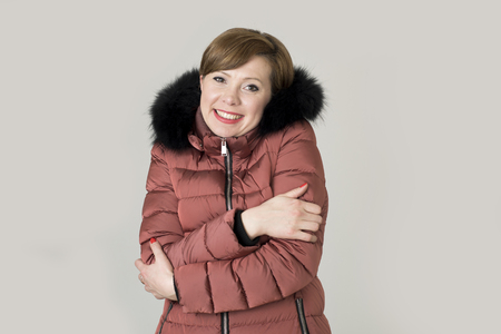 young read hair attractive and sweet woman 20s or 30s posing isolated wearing warm winter jacket with fur hood shivering and freezing feeling cold in sweet face expression