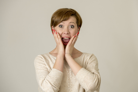 young happy and surprised red hair woman looking to camera delighted astonished and in surprise face expression isolated on grey background in emotions concept