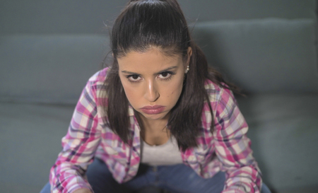close up portrait of young attractive and sad hispanic woman sitting at home couch looking stressed and worried in domestic problem and lifestyle concept
