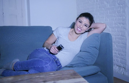 Young beautiful and happy latin woman on her 30s holding TV remote enjoying at home living 版權商用圖片