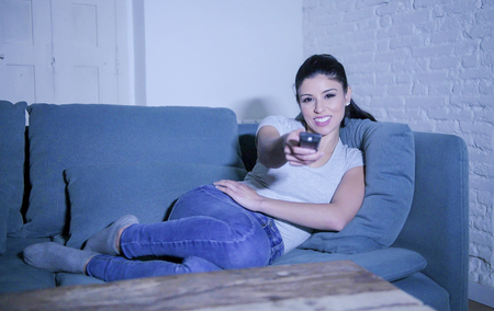 young beautiful and happy hispanic woman on her 30s holding TV remote enjoying at home living room couch watching television show comedy movie smiling having fun relaxed in lifestyle