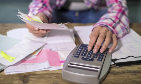 faceless anonymous woman hands working with bank paperwork bills and financial documents calculating monthly expenses and debt with calculator and laptop in domestic accounting concept