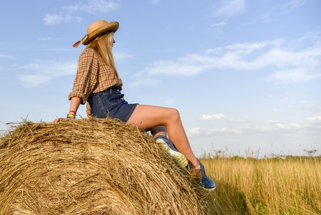 Cheerful young girl sitting on a haystack in the middle of a wheat field looking into the distance sunset