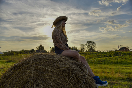 Girl in a wheat field sitting on a haystack in a hat and jeans watching the sunset Standard-Bild