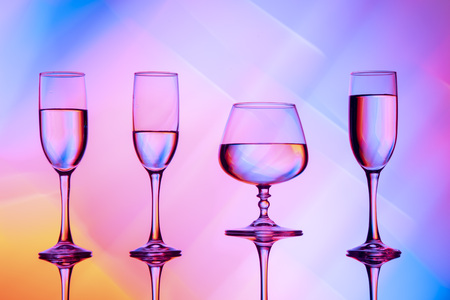 Four wine glasses of water are on the table, behind a colorful background.Glasses reflected