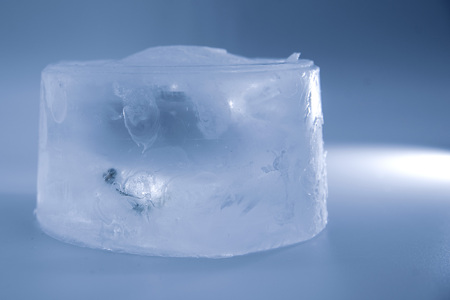 A piece of ice on a blue background blue white