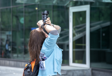 girl photographer shoots the sky against the wall of the business center.