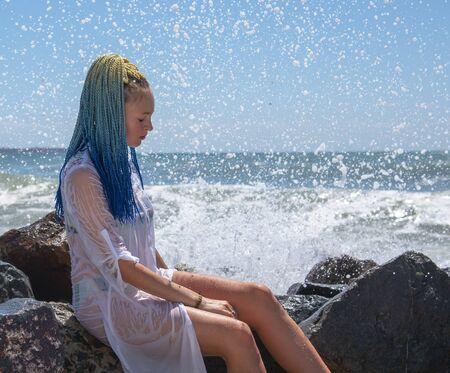 Auf den Steinen sitzt ein Mädchen mit blauen senegalesischen Zöpfen.