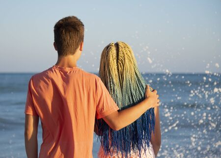 Two teenagers embracing stand with his back to the camera and look at the waves crashing on the rocks.The spray flies in all directions.The girl with the blue Senegalese braids. Foto de archivo
