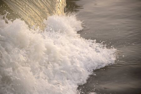 Large waves and sea foam illuminated by the evening sun. The water shines like metal.