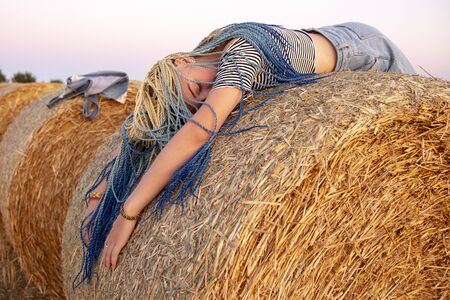 Girl with Senegalese pigtails lying on his stomach on a haystack.Braids close to her face. Фото со стока